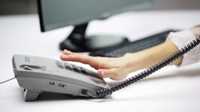 Woman hand dialing number on telephone at office stock video