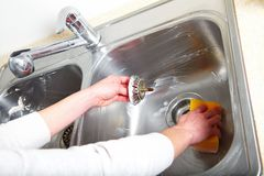 Cleaning sink. Woman hand doing chores in the kitchen at home , cleaning sink and faucet Stock Photos