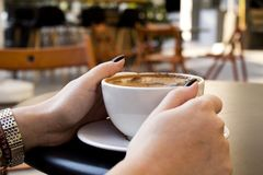 Woman hand drinking coffee in cafe royalty free stock image