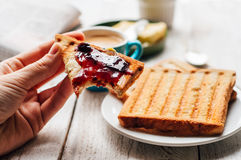 Woman hand eating toast for breakfast Royalty Free Stock Photography