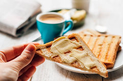 Woman hand eating toast for breakfast Royalty Free Stock Images