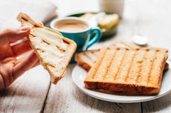 Woman hand eating toast for breakfast Royalty Free Stock Image