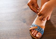 Woman hand fastens strap on leather shoes sandals Stock Photos