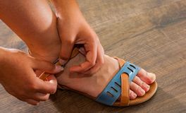 Woman hand fastens strap on leather shoes sandals Royalty Free Stock Images