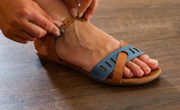 Woman hand fastens strap on leather shoes sandals Stock Image