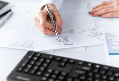 Woman hand filling in invoice paper Royalty Free Stock Image