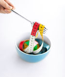 Woman hand with fork, bowl and measuring tape Stock Photo