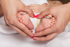 Woman hand forming heart around the foot of a baby with wedding rings parents Stock Photography