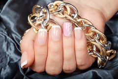 Woman hand with french manicured nails holding a chain necklace. Hand with beautiful short french manicured nails holding a chain necklace Royalty Free Stock Photography