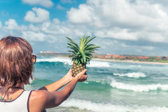 Woman hand with fresh exotic pineapple fruit on the ocean background. Fresh healthy diet food concept. Bali island. Royalty Free Stock Photo