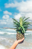 Woman hand with fresh exotic pineapple fruit on the ocean background. Fresh healthy diet food concept. Bali island. Stock Image