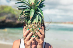 Woman hand with fresh exotic pineapple fruit on the ocean background. Fresh healthy diet food concept. Bali island. Stock Photo