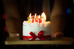 Woman hand giving delicious birthday cake with burning candles. In the party Royalty Free Stock Photo