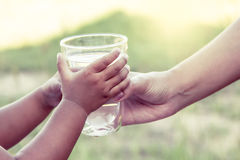 Woman hand giving glass of fresh water to child in the park Royalty Free Stock Photography