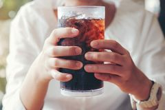 Woman hand giving glass ,Soft drinks with ice, sweethart or budd. Y Stock Photo