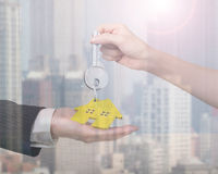 Woman hand giving key with house keyring to man hand Royalty Free Stock Photography
