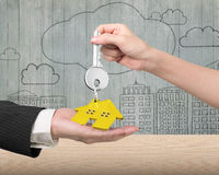 Woman hand giving key with house keyring to man hand Stock Photos