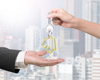 Woman hand giving key with house keyring to man hand Stock Images