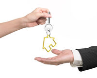 Woman hand giving key with house keyring to man hand Stock Image