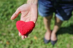 Woman hand giving red hand-made crocheted heart with green grass background and copy space. Valentine`s Day. Symbol of love. Woman hand giving red hand-made Stock Photography