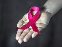 Woman hand giving satin pink ribbon. Royalty Free Stock Images