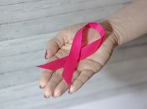 Woman hand giving satin pink ribbon. Stock Photos