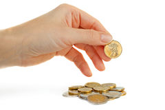 Woman hand with golden coin and coins. Royalty Free Stock Image