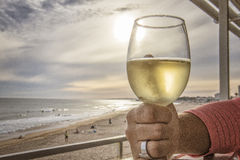 Woman hand grabbing glass of white wine overlooking the beach wi. Th sunset stock photos