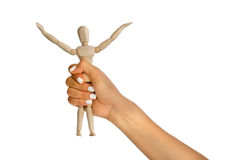 Woman hand grabs little puppet Royalty Free Stock Photo