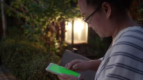 Woman hand with green screen in smart phone at garden in the evening. stock footage