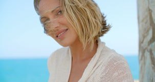 Woman with Hand in Hair in front of Blue Ocean stock footage
