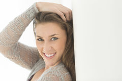 Woman With Hand In Hair Leaning On Wall Royalty Free Stock Photography
