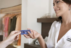 Woman hand Handing Credit Card at Counter Stock Image