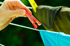 Woman hand hanging wet clothes on rope line Royalty Free Stock Photos