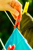 Woman hand hanging wet clothes on rope line Stock Photography