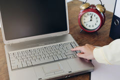 Woman hand and her finger pressing a button on a laptop on a woo Stock Photography