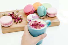 Woman hand hold blue cappuccino cup with roses petals and beauty macarons on wood desk Royalty Free Stock Images