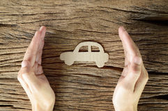 Woman hand hold brown paper car. Shape on wooden background - protection of car concept Stock Image