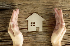 Woman hand hold brown paper house. Shape on wooden background Stock Image