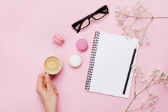 Woman hand hold cup of coffee, cake macaron, clean notebook, eyeglasses and flower on pink table from above. Female working desk. Cozy breakfast. Flat lay royalty free stock image