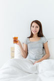 Woman hand hold a cup of tea on the bed Stock Photos