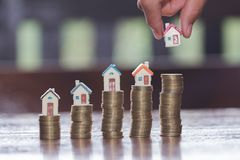 Woman hand hold a home model put on the stack coin with growing. Savings money for buy house and loan to business investment for real estate concept. Invesment stock images