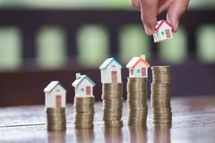 Woman hand hold a home model put on the stack coin with growing. Savings money for buy house and loan to business investment for real estate concept stock photo