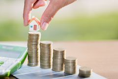 Woman hand hold a home model put on the stack coin with growing. Savings money for buy house and loan to business investment for real estate concept stock images