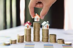 Woman hand hold a home model put on the stack coin with growing. Savings money for buy house and loan to business investment for real estate concept. Invesment stock photo
