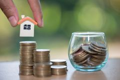 Woman hand hold a home model put on the stack coin with growing. Savings money for buy house and loan to business investment for real estate concept. Invesment stock photography