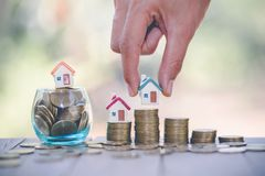 Woman hand hold a home model put on the stack coin with growing, Savings money for buy house and loan to business investment for. Real estate concept. Invesment royalty free stock image