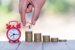 Woman hand hold a home model put on the stack coin with growing, Savings money for buy house and loan to business investment for. Real estate concept. Invesment stock photos
