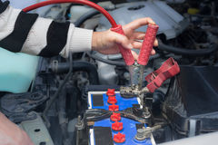 Woman hand hold jumper cables to car battery Stock Image