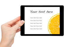 Woman hand hold a mini tablet with orange Royalty Free Stock Images